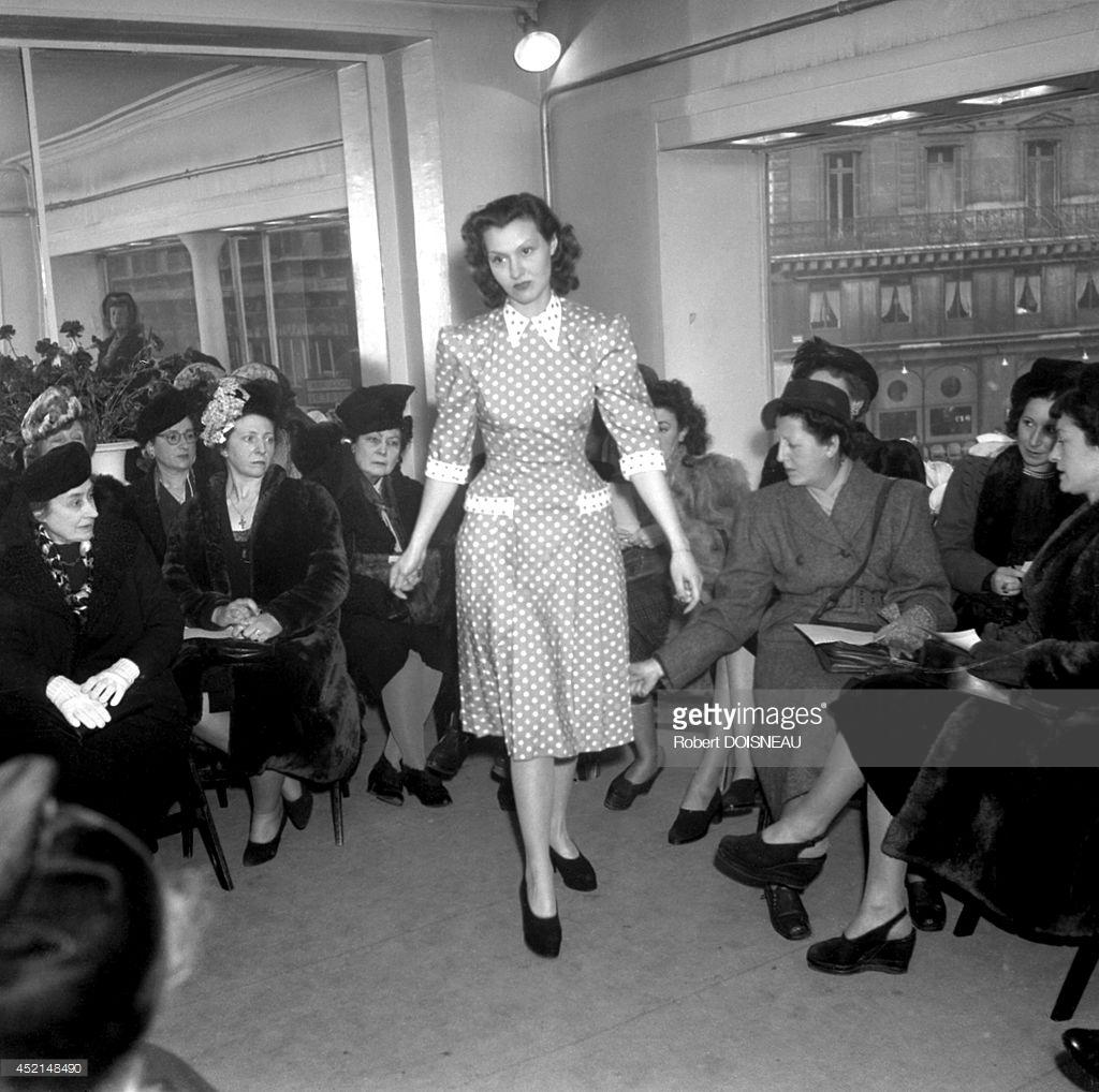 1947. Модель, идущая по подиуму во время зимнего показа моды