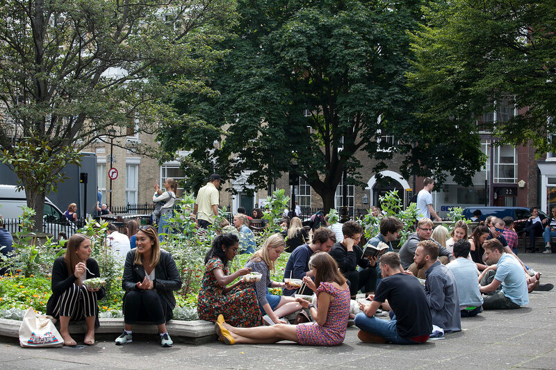 Office clerks sit on the grass and dine at Golden Square, Soho, exposing faces to the sun