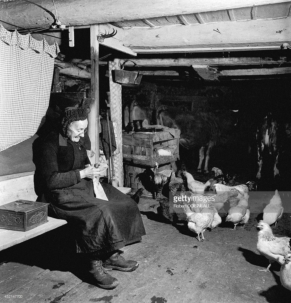 1947. Старушка сидит и вяжет в своем доме в Сен-Веране