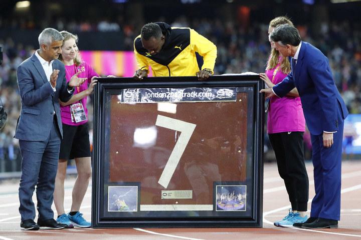 Организаторы подарили Болту фрагмент памятной беговой дорожки Олимпийского стадиона под номером 7, н