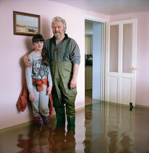 Дэйв и его 12-летняя дочь позируют в своем затопленном доме в деревушке Барроубридж, графство Сомерс