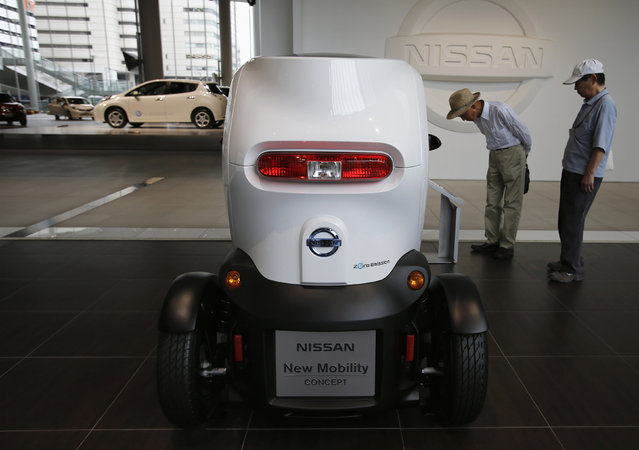 Visitors look at Nissan Motor Co's New Mobility concept car at the company's showroom in Y