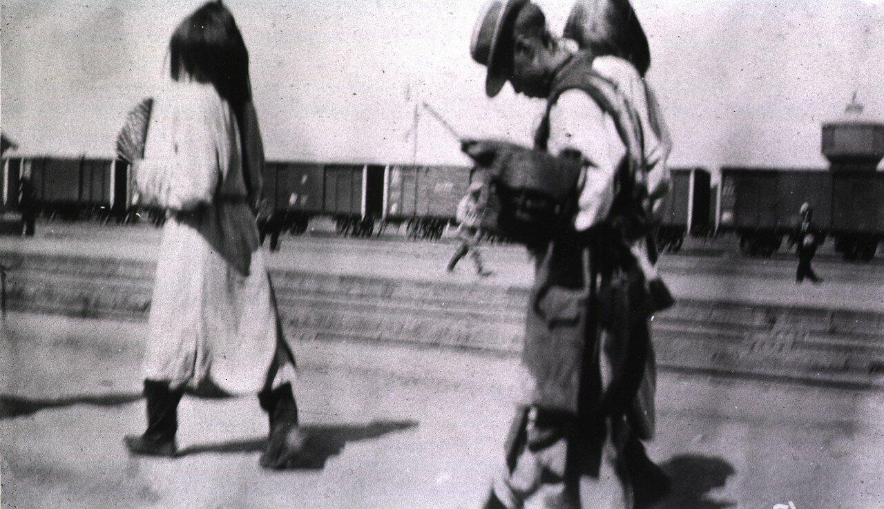 Китайский генерал идет впереди двух служащих на железнодорожной станции в Харбине