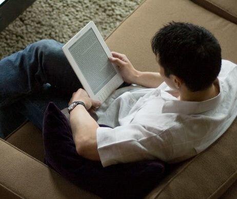 Amazon Kindle DX в руках молодого человека, читающего книгу где-то в парке