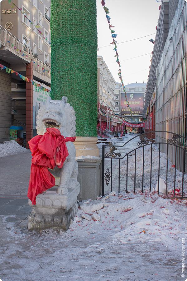 бетонный лев с красным тряпичным шарфом на улице в Маньчжурии