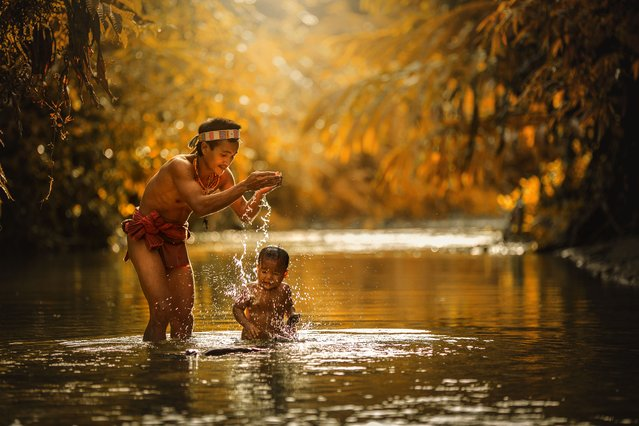 A Mentawai warrior washes a young child in the river on July 19, 2014 on the Mentawai Islands, Indon