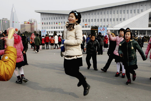 North Korean students skip rope as they gather on the plaza in front of the ice rink for Lunar New Y