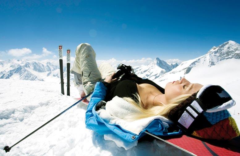 сексуальная девушка отдыхает, лежа на снегу на горе