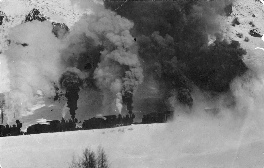 Smoke rises from Denver and Rio Grande locomotives that push a train on an unidentified pass probably in Colorado, between 1900 and 1920.