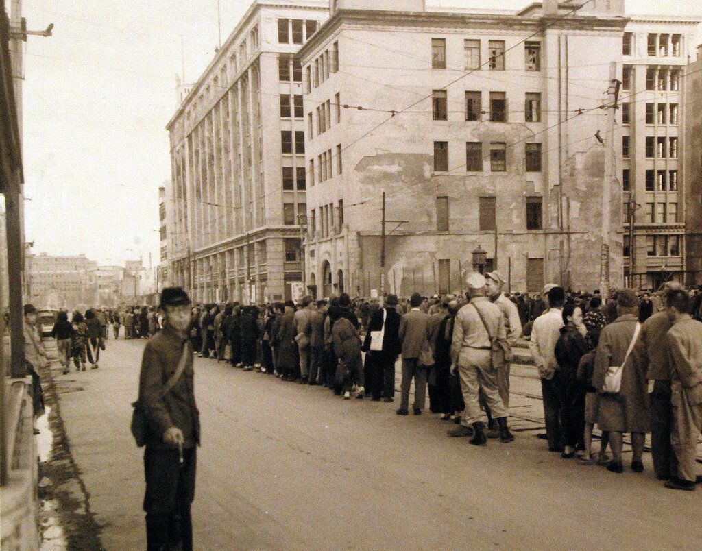 Scene at Sasebo, Kyushu, shows people lined up for trolley car on Ginza Street. October 19, 1945