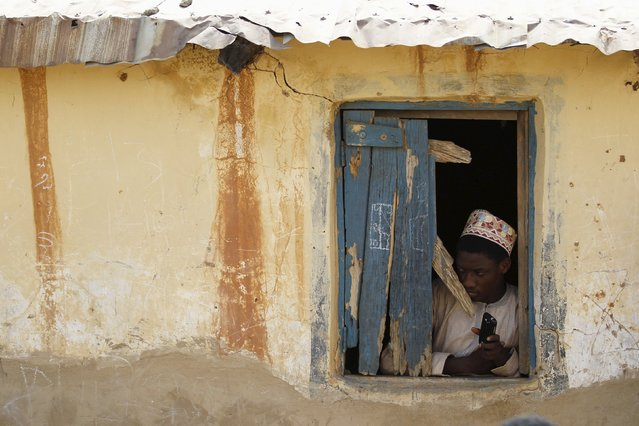 A boy looks through a broken window at a local Islamic school in Zaria, Kaduna state, Nigeria, Febru
