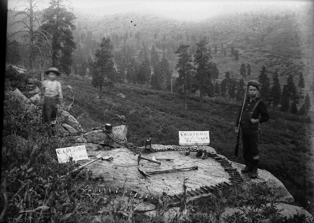 """Two boys hold rifles by a model railroad creation identified as """"A Question of Right of Way"""" in the La Sal Mountains, Utah. 1897 Sep. 3"""