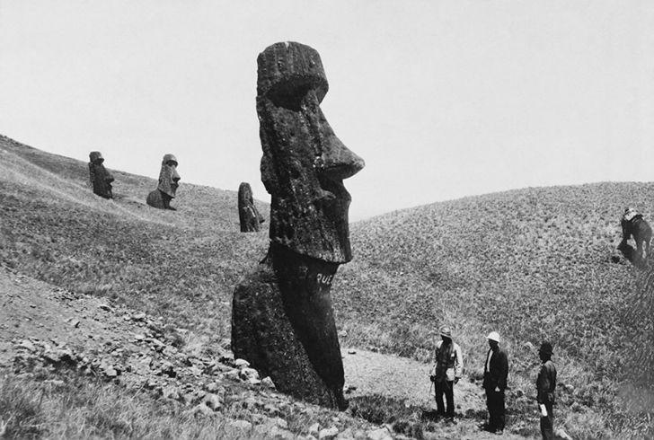 Мужчины осматривают моаи, огромные каменные статуи на острове Пасхи, декабрь 1922 года.