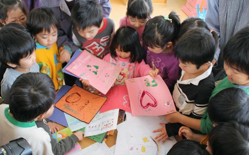 Воспитанники детского сада Фукусимы рассматривают письма детей изДоминиканской Республики. Больше 2