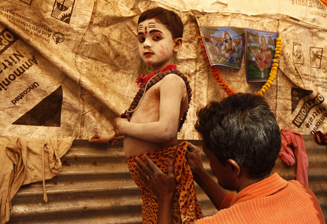 Sumanta Das, 8, is dressed up as Lord Shiva by his father to get alms from pilgrims at a make-shift