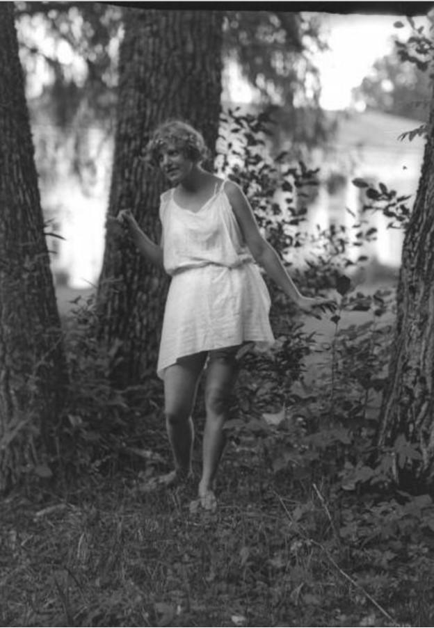 Девушка в тунике среди деревьев