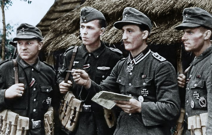 color Oberfeldwebel Hubert Pilarski giving orders to three experienced Gruppenführer.jpg