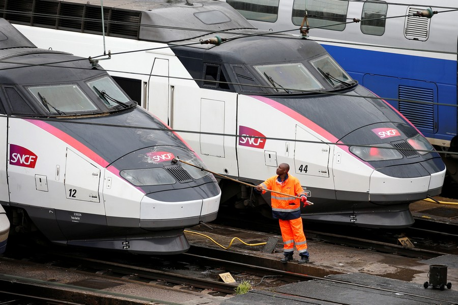 A worker cleans up a French TGV train parked at a SNCF depot station in Charenton-le-Pont near Paris