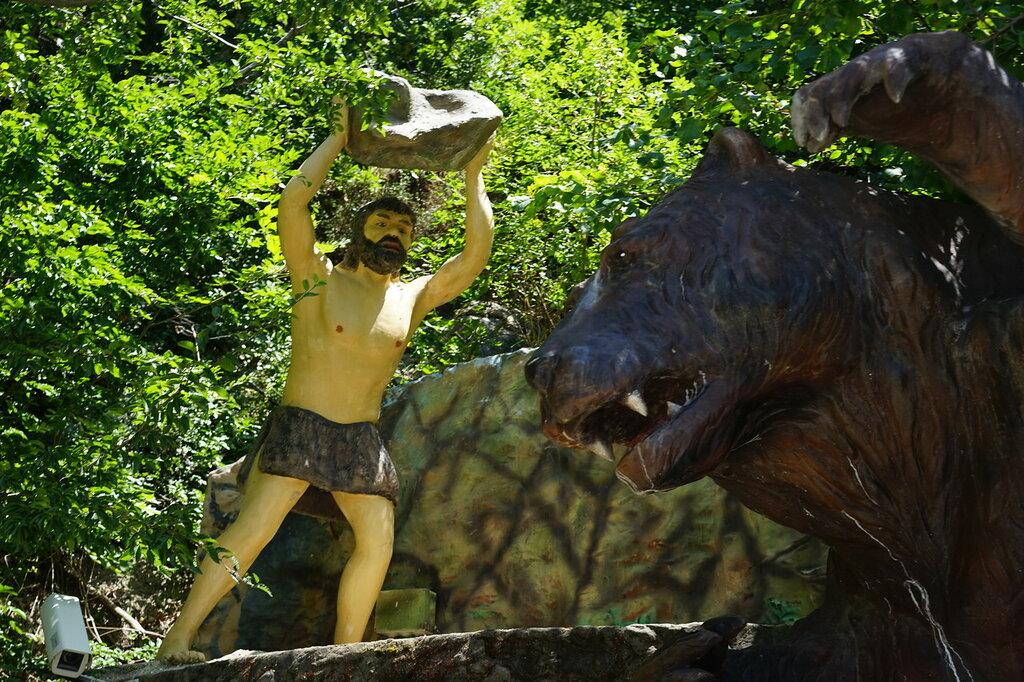 Древний человек перед броском камня в медведя. Искусственная Медвежья пещера в Сафари-Парке в Геленджике