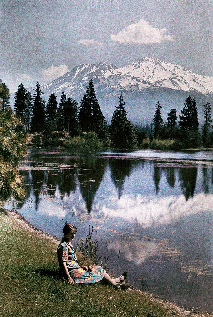 1929. США.  Девушка сидит на берегу озера на фоне заснеженных гор, Калифорния