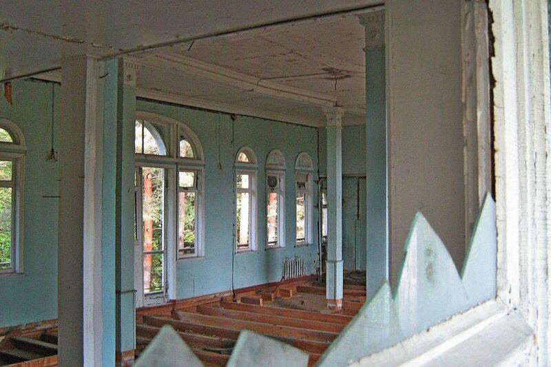 Разобранный пол внутри дебаркадера сквозь разбитое окно с осколками стекла
