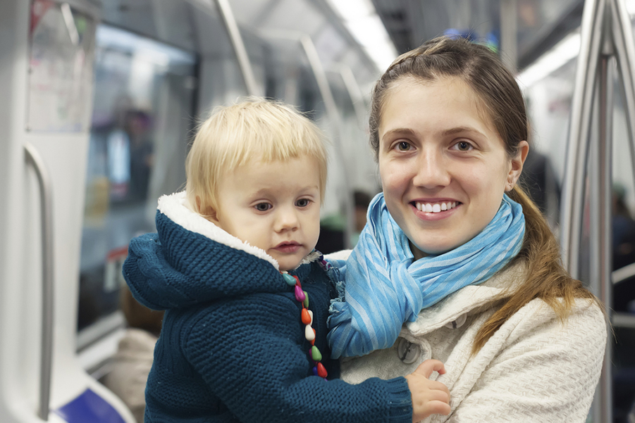 Smiling woman with baby in subway