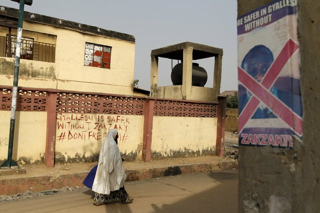 A woman walks past a house that was damaged during recent clashes between Shi'ites and the army