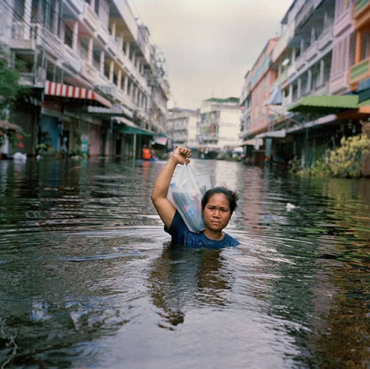 Таиланд, 2011. Городок затопило, но женщина все равно идет в магазин, чтобы купить продукты для свое