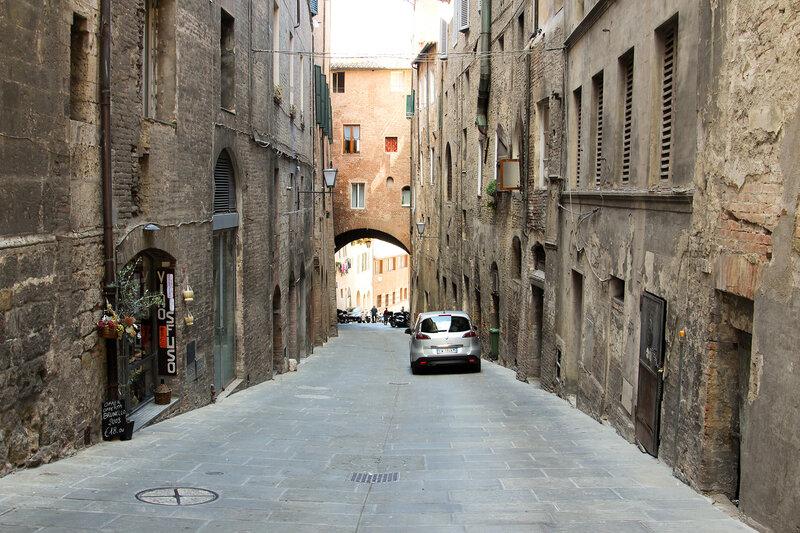 Узкая улочка с каким-то автомобилем в городе Сиена