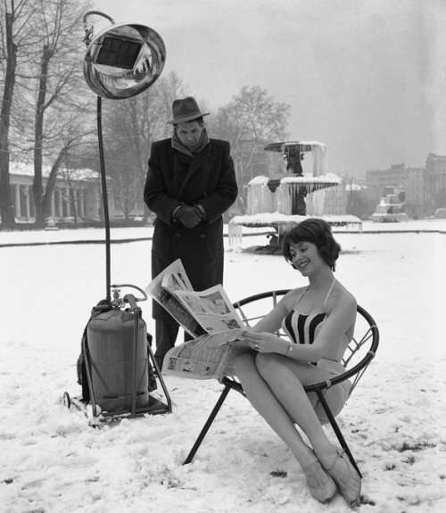 Marion Liebig, AKA Miss Hesse 1959, keeps warm under the artificial sunshine of a gas-powered infra-red lamp in a snow-covered park in Wiesbaden, Germany, 1960.jpg