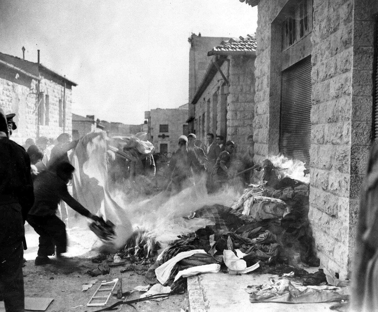Толпа демонстрантов-арабов сжигают вещи, взятые из еврейских домов в Иерусалиме. Январь