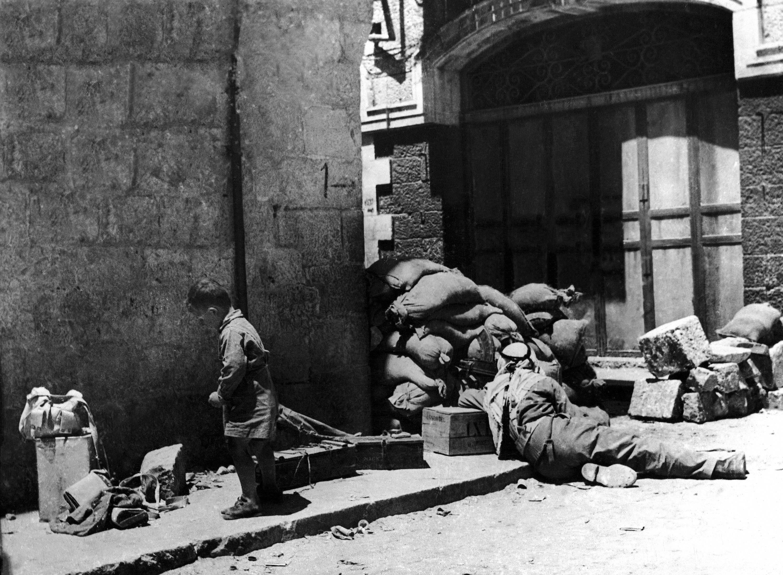 Арабский солдат с пулеметом, укрывается за мешками с песком на улице возле Новых ворот в старом городе Иерусалима. 29 мая