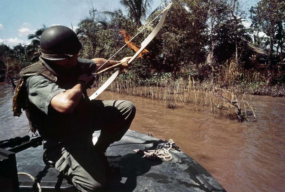 Лейтенант Дональд Шеппард стреляет горящими стрелами в направлении бамбуковой хижины на берегу реки Bassac, под которой может находиться подземный бункер вьетнамских партизан