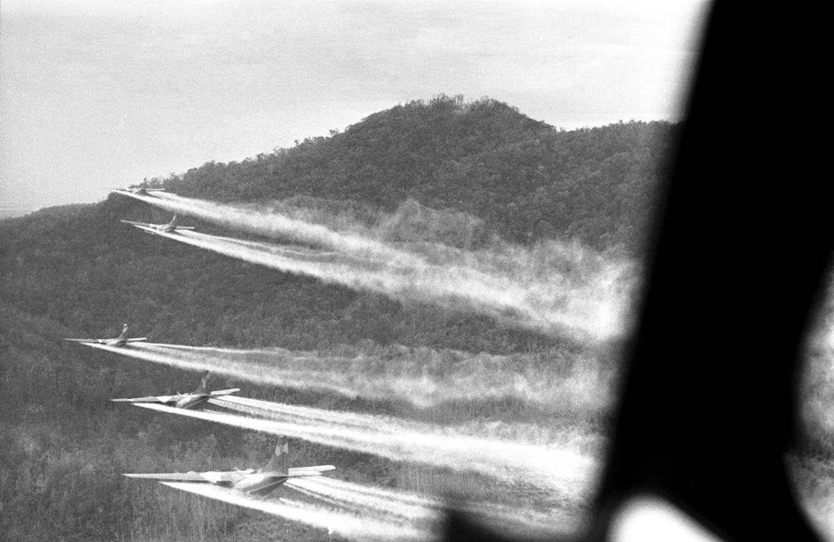 Распыление дефолиантов (химических веществ, истребляющих все живое) над джунглями: 5 американских военно-транспортных самолетов C-123 Provider на бреющем полете  к западу от города Хюэ