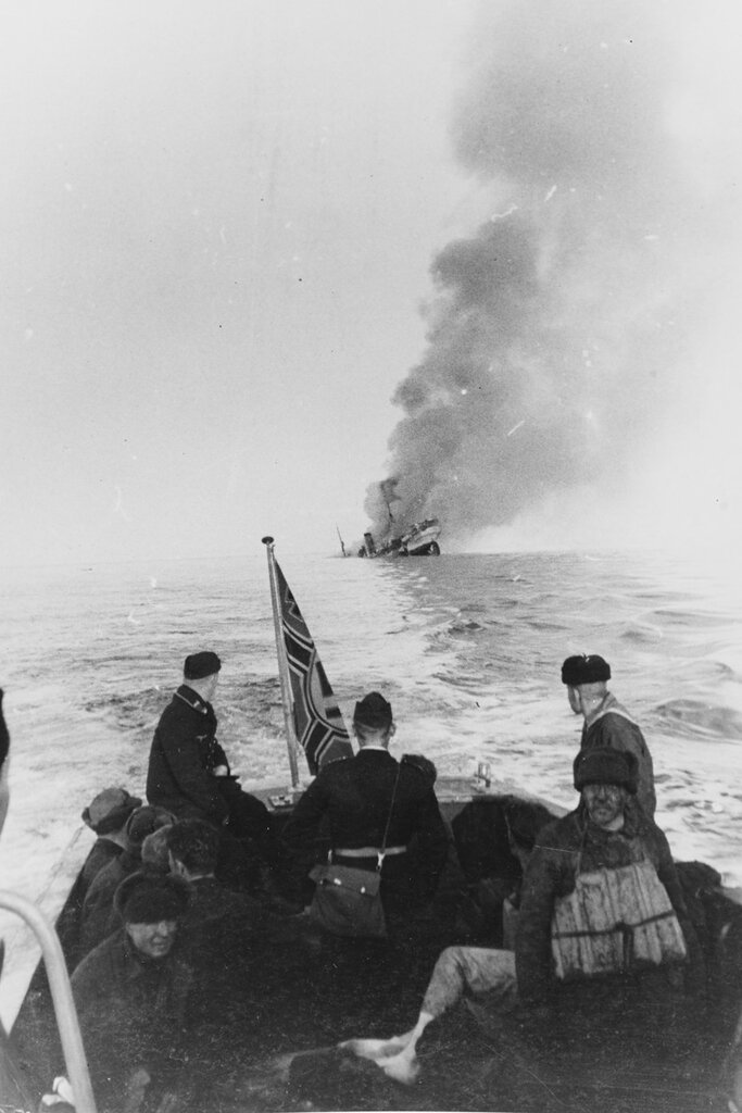 Sinking Of The Russian Icebreaker ALEXANDER SIBIRIEKOV. After being attacked by the German cruiser ADMIRAL SCHEER, in the Barents Sea in August 1942. Survivors of the sinking ship have been rescued by the SCHEER'S launch
