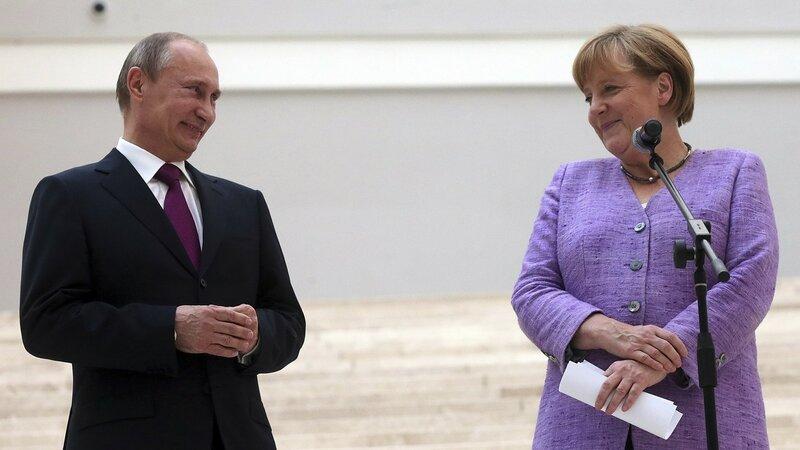 Russian President Vladimir Putin President and German Chancellor Angela Merkel visit the State Hermitage Museum in St. Petersburg