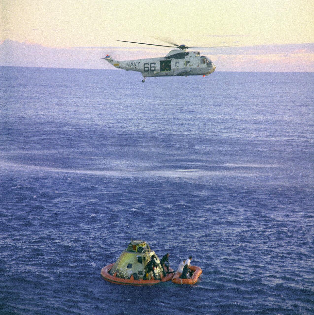 1969, 26 мая. Спуск отсека экипажа на парашютах наблюдали с корабля и передавали по телевидению. Приводнение произошло через 40 минут после восхода Солнца в месте посадки.Астронавты открыли люк, были подняты на борт вертолёта и доставлены на авианосец