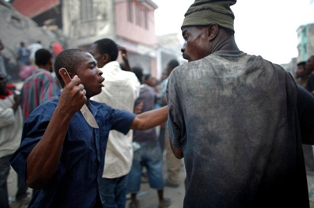 Анархия на Гаити A looter holds a knife as he fights for products after Tuesday's earthquake in Port-au-Prince