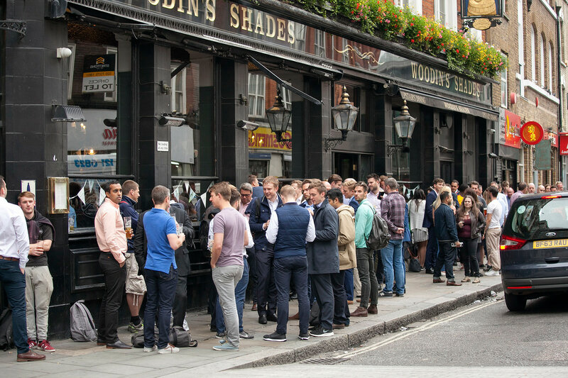 A motley crowd sits outside the pub, drinks beer, talks with friends. Borough market