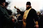 Игумен Меркурий (Иванов) окропляет святой водой принесенную верующими воду в праздник Крещения Господня.