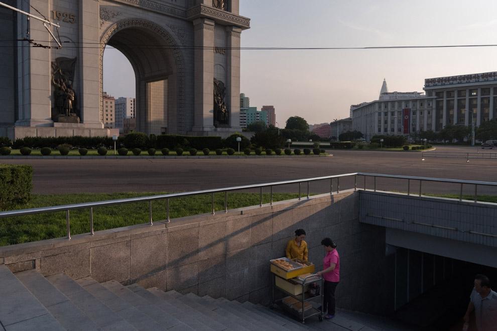 10. Пхеньян строится. Видны высотные дома. Забором огорожена очередная стройка.