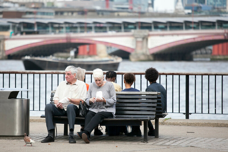 An elderly couple eating popcorn, sitting on a bench overlooking the Thames. South Shore of the Thames