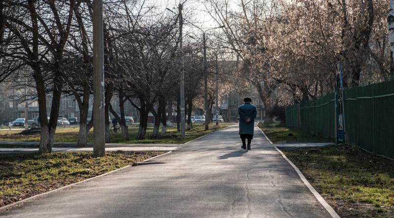 пожилая женщина прогуливается весной по тратуару