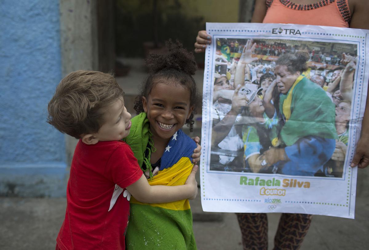 10. Друг обнимает четырехлетнюю Джовану Силву — кузину дзюдоистки Рафаэлы Силвы, выигравшей золото н
