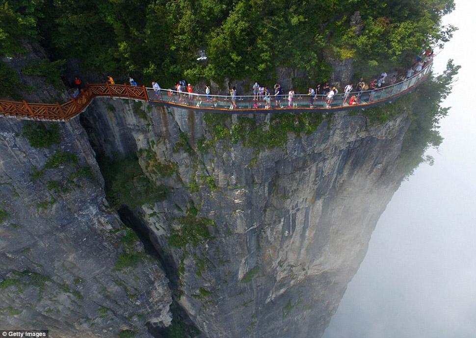 На снимках видно, как первые посетители открывшегося моста аккуратно идут вдоль горы, держась за сте