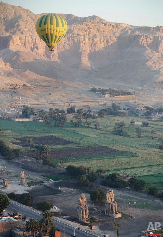 Воздушный шар летит над колоссами Мемнона на западном берегу реки Нил в Луксоре, Египет. Только с воздушного шара, поднявшись высоко в небо ранним утром, туристы могут понять красоту древностей этой столицы Древнего Египта когда-то известной, как Фивы.