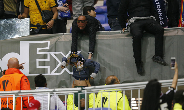A Lyon fan helps another fan out of the stands as fans clash