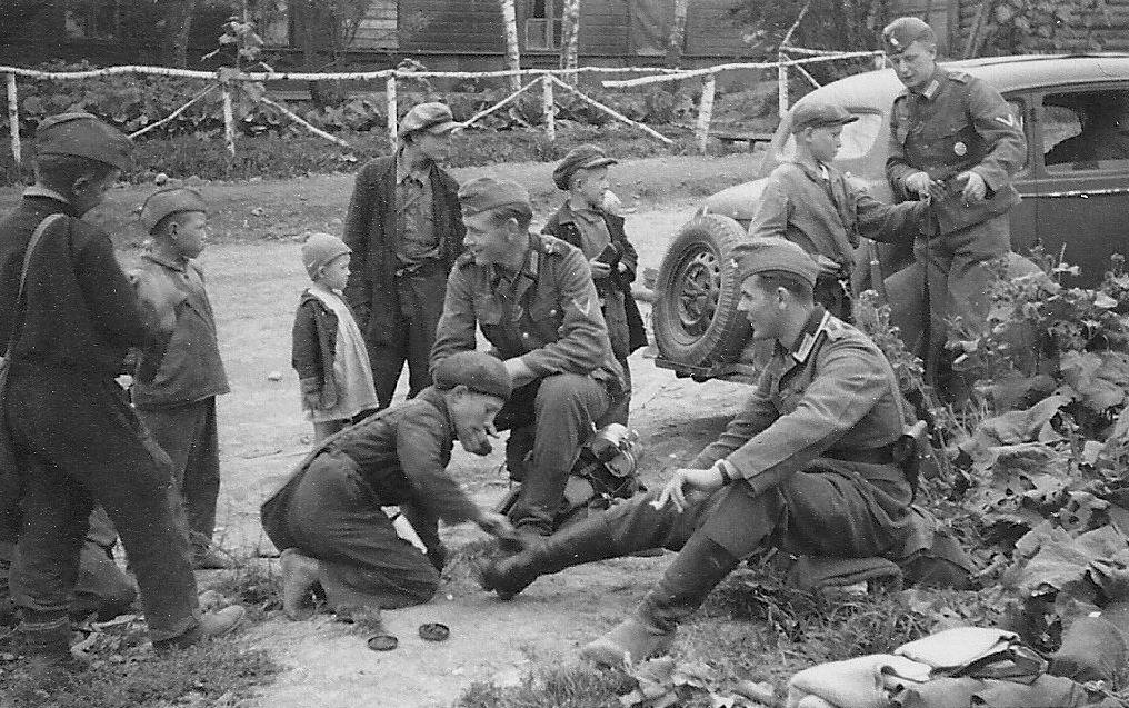 Мальчик чистит сапоги немецкому солдату.