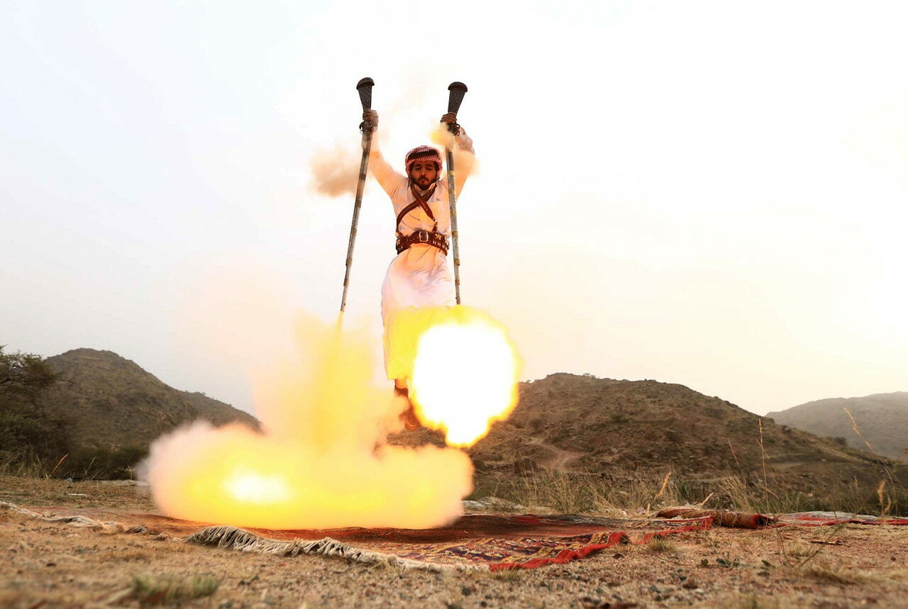 Man fires weapons as he dances during a traditional excursion near the western Saudi city of Taif