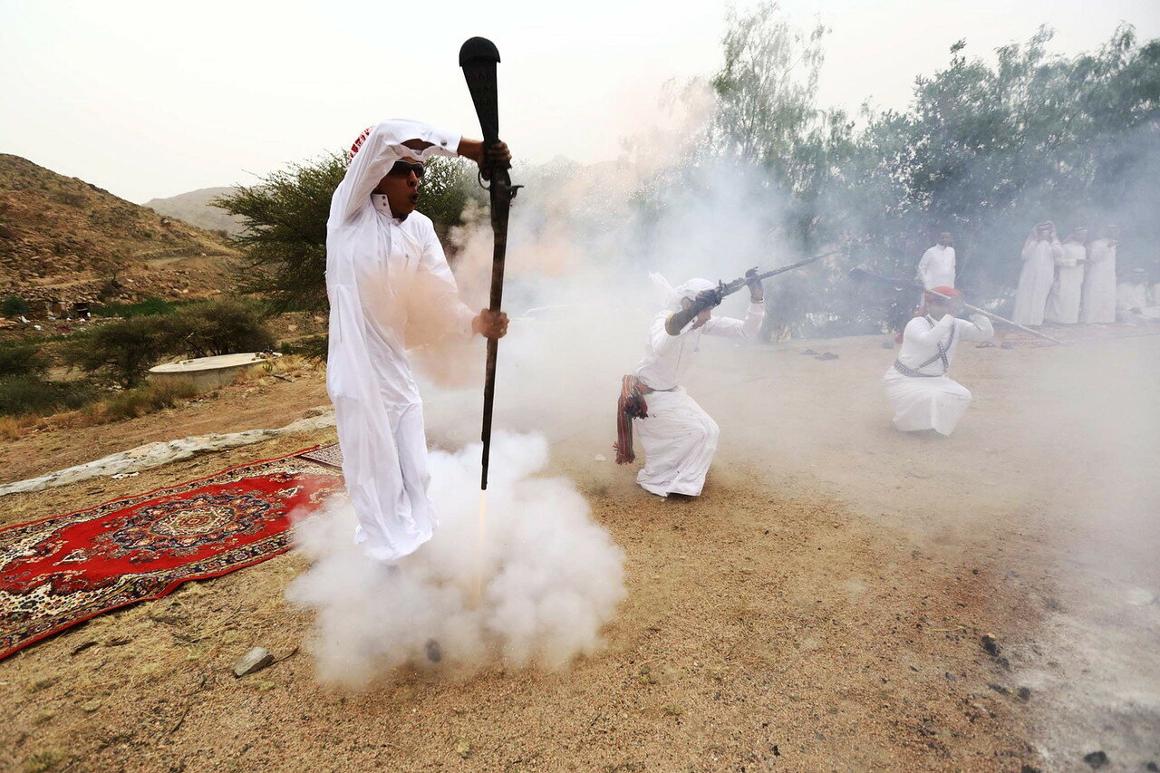 A man fires a weapon as he dances during a traditional excursion near the western Saudi city of Taif